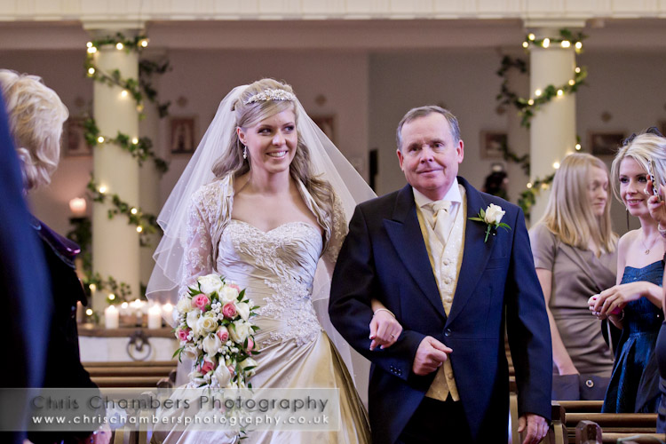 Walking down the aisle, a bride walks down the aisle in the chapel at Hazlewood castle near York