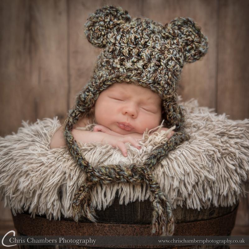 Baby wearing big hat on newborn baby photo shoot